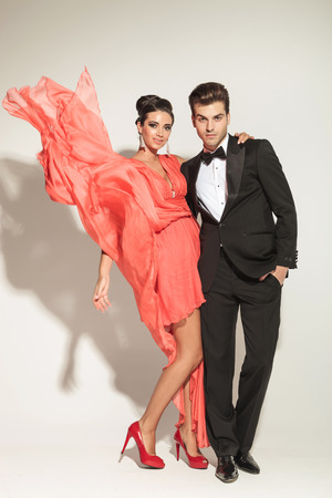 together with long tie: Handsome young fashion man embracing his lover while she is fluttering the dress. Stock Photo