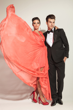 together with long tie: Full body picture of a young fashion couple posing on grey studio background. The woman is fluttering her dress while holding one hand on her lovers shoulder. Stock Photo