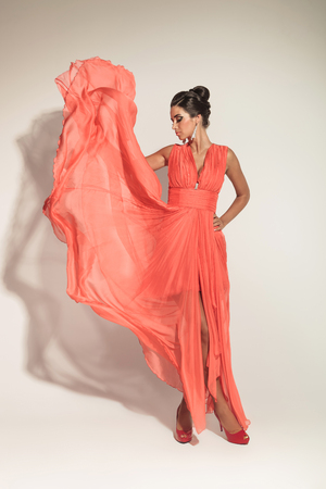 fluttering: Elegant fashion woman looking down while fluttering her coral dress.