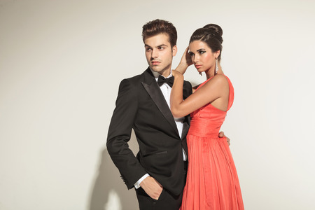together with long tie: Hermosa mujer elegante fijaci�n de su cabello mientras que su amante est� buscando fuera con una mano en el bolsillo.