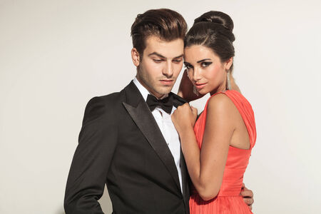 romantically: Close up picture of a young elegant couple embracing, the man is looking down while the woman is looking at teh camera. Stock Photo