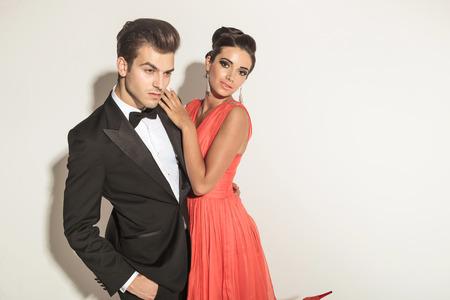 together with long tie: Hermosa mujer de moda joven que abraza a su amante mientras �l est� sosteniendo una mano en el bolsillo, mirando hacia abajo.
