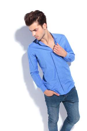 man looking down: Young fashion man looking down while pulling his blue shirt.