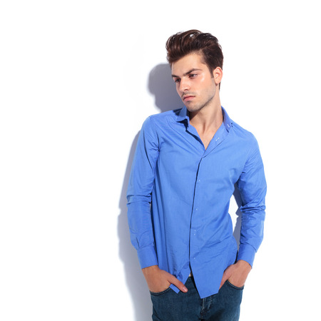 man looking down: Fashion man looking down with his hands in pockets while leaning on a white wall. Stock Photo