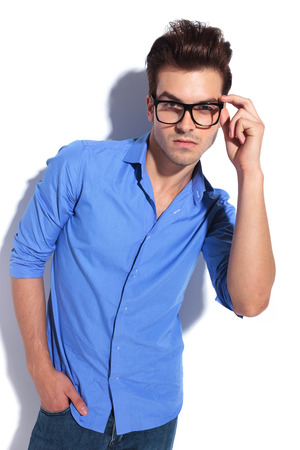 hand in pocket: Attractive business man fixing his glasses while looking at the camera, holding one hand in his pocket.