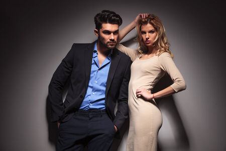 black man white woman: Young fashion business man looking away with his hands in pockets while his lover is leaning on him and fixing her hair.