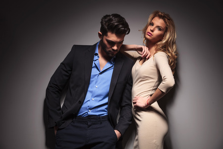 man looking down: Attractive young business man looking down with his hands in pocket while his girlfriend is leaning on him, looking at the camera. Stock Photo