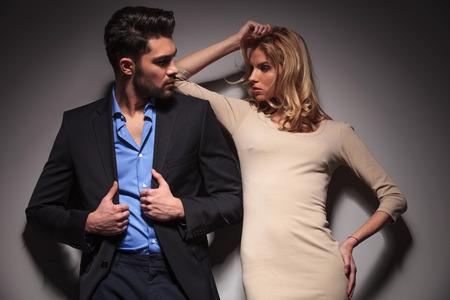 modelos hombres: Joven pareja de moda mirando el uno al otro, la mujer es la fijaci�n de su cabello, mientras que el hombre es la fijaci�n de su chaqueta, ambos mirando a otro lado.