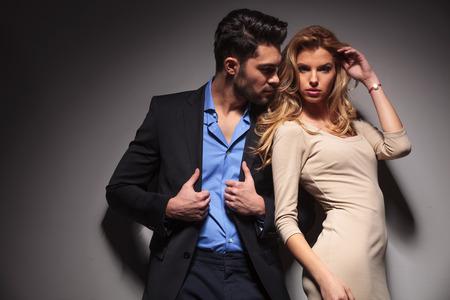 poses de modelos: Hombre de negocios atractivo que fija su chaqueta mientras mira a su amante. La hermosa mujer rubia est� arreglando su cabello mientras mira a la c�mara. Foto de archivo