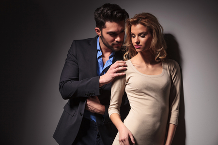 handome: Handome young business man looking at his lover while toching her shoulder with his right hand.