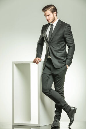 Full length picture of a elegant business man looking down while leaning on a white modern table.