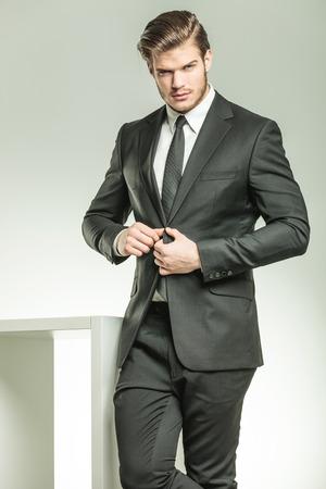 Bel homme d'affaires élégant en regardant la caméra tout en fermant sa veste.