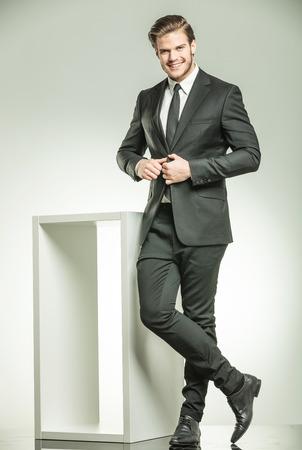 traje: Feliz joven hombre de negocios sonriente mientras se cierra la chaqueta. Haci�ndose pasar cerca de una mesa blanca y moderna sobre fondo de estudio. Foto de archivo
