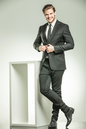 cute guy: Happy young business man smiling while closing his jacket. Posing near a white modern table, on studio background.