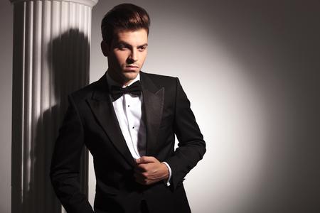 elegant business man: Young elegant business man posing near white column while fixing his jacket.