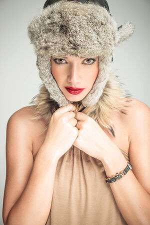 Young beautiful woman pulling her fur hat on while looking at the camera photo
