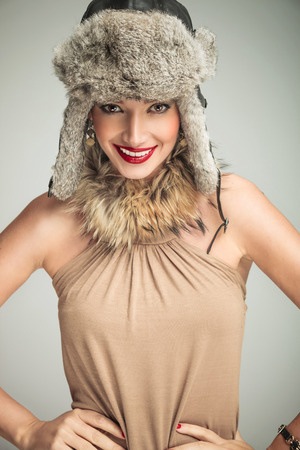 happy smiling beauty woman wearing fur hat and collar standing with hands on hips and looks to the camera photo