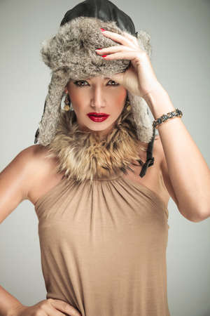 sexy beautiful woman in luxury clothes and fur hat standing with one hand on hip and one holding her hat photo