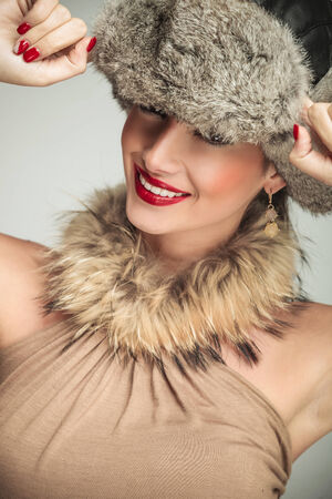 portrait of a beauty woman wearing a fur hat and smile to the camera, hand on cap photo