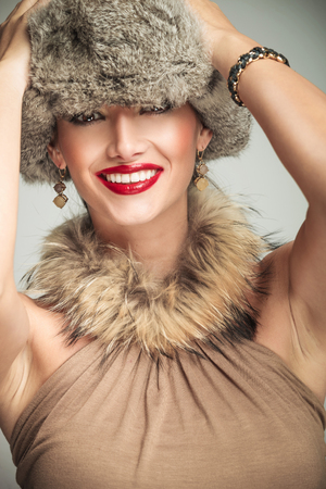 young beautiful woman laughing while holding hands on her fur hat photo
