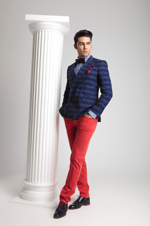 Handsome young fashion man posing near white column with both hands in his pocket. Full body picture. photo