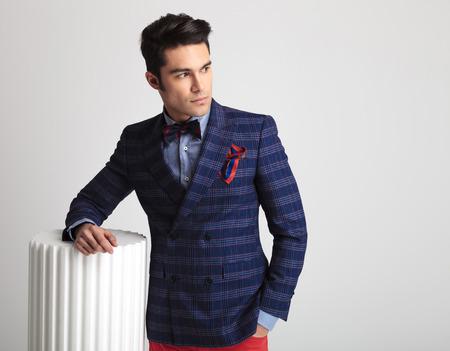fashion: Jeune homme de la mode en regardant loin de la caméra tout en maintenant un bras sur une colonne blanche.