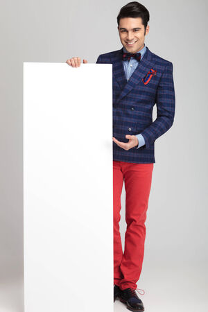 casual fashion: Full body picture of a young casual fashion man presenting a white empty board.