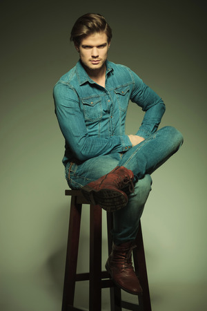 man legs: Handsome young casual man sitting on a stool with his legs crossed, looking at the camera.