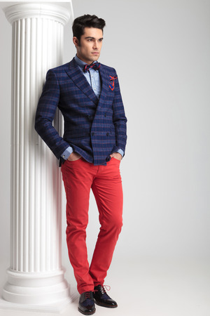 Ful length picture of a handsome young fashion man leaning on a white column holding both hands in pockets.