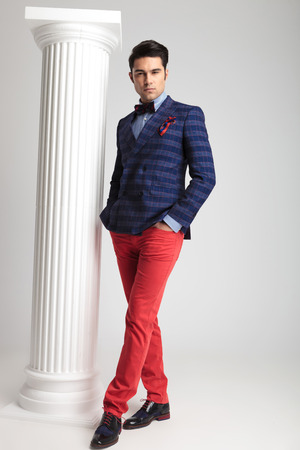 Full body picture of a smart casual fashion man holding one leg in front of the other and his hands in pockets. photo