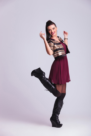 Full body image of a happy young fashion woman lifting one leg and both hands in the air. photo