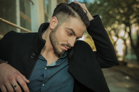 man hair: Casual fashion man looking down while fixing his hair, close up picture. Stock Photo