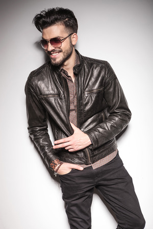 Happy young fashion man smiling while looking away, holding his thumb in his jacket. Imagens