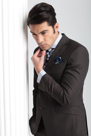 man looking down: Handsome business man looking down while holding his hand to chis chin thinking.