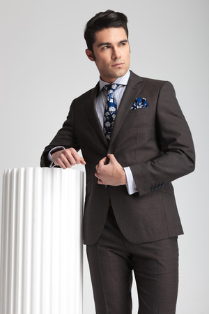 cerrando negocio: Hombre de negocios joven cerrando su chaqueta mientras se apoya en una columna blanca, mirando a la cámara. Foto de archivo