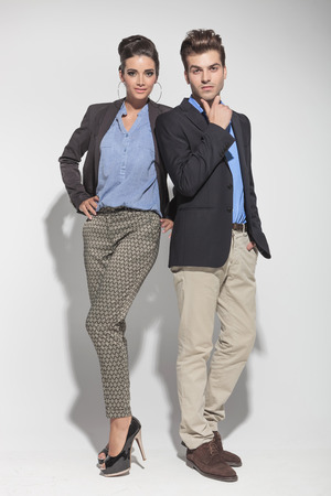 full lenght: Full lenght picture of a young fashion couple posing on light grey background, both looking at the camera.
