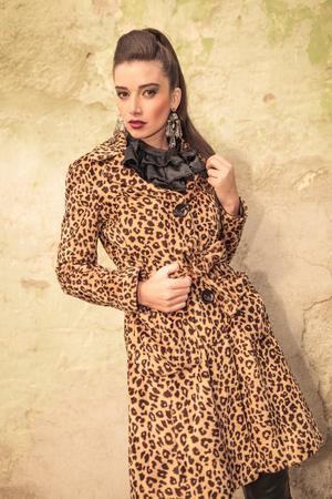 Elegant fashion woman posing near a wall, looking at the camera. photo