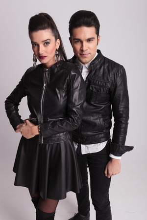 Young fashion couple posing on grey studio background, the woman is holding her hands together. photo
