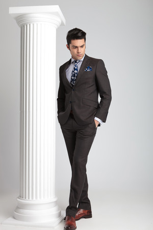 man looking down: Full length picture of a young business man looking down while holding both hands in his pockets. Stock Photo
