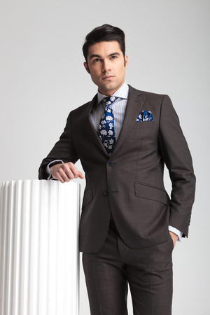 lean on hands: Attractive young business man holding one hand in pocket while leaning on a white column, on grey studio background.