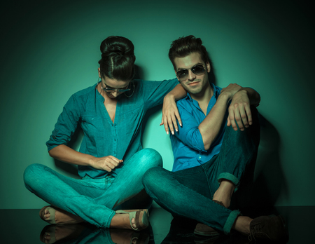 woman looking down: Fashion woman looking down and  arranging her shirt while her lover is sitting next to her looking at the camera. Stock Photo
