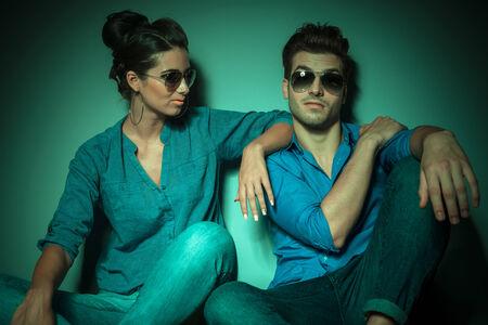 poses de modelos: Atractiva mujer de moda joven que busca a su amante mientras que él está mirando a la cámara.