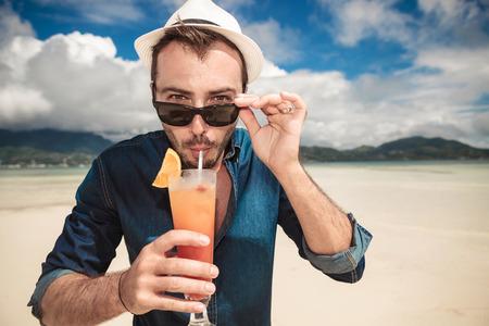 Close-up foto van een casual jonge man op het strand drinken van een oranje cocktail met een rietje terwijl opstijgen zijn zonnebril.