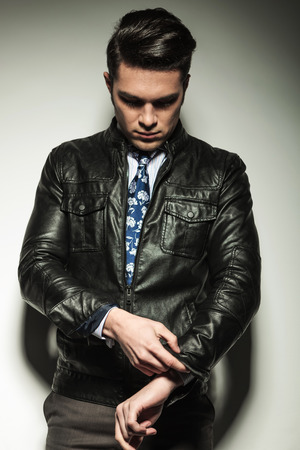 fixing: Business man in leather jacket, looking down while fixing his sleeve. On grey atudio background.