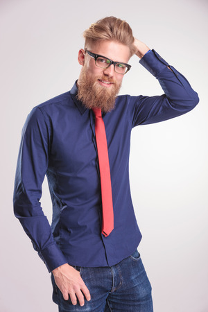 blue shirt: Portrait of a young casual man smiling at the camera while fixing his hair. He is also holding a thumb in his pocket. Stock Photo