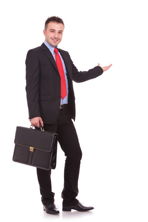 business case: Side view picture of a handsome young business man holding a black brief case while presenting.