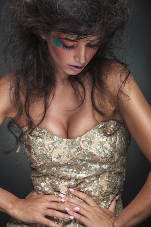 waist down: Glamorous fashion woman looking down while posing with her hands around her waist, on dark studio background.