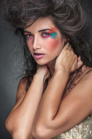 Gorgeous woman with colorful make up looking at the camera while holding both hands to her neck. photo