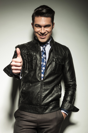 Happy business man wearing leather jacket, holding one hand in his pocket and showing the thumbs up sign with the other one. photo