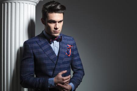 uomo rosso: Immagine di un giovane uomo di moda guardando verso il basso, mentre in posa vicino a colonna bianca. Archivio Fotografico